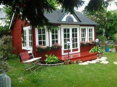 Wie gemütlich! Das schwedenrote Gartenhaus im Clockhouse-Stil wird durch eine Mini-Terrasse und Zierbeete ergänzt. Auch Blumenkästen vor den weiß-gerahmten Fenstern sehen toll aus!