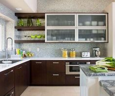 A seamless mix of many popular trends -- open shelving, metal framed uppers, two toned countertops and base cabinetry, plus an intricately tiled backsplash
