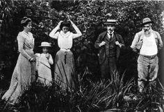 Клод Моне с семьей Дюран-Рюлову у водяных лилий в саду летнего загородного дома Моне в Живерни. Фотография. Повседневные костюмы упростились, женские юбки сузились, мужской костюм состоит из пиджака, жилета и брюк.