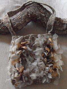 borsa di cotone a tracolla color melange noce-ecru, realizzata a uncinetto e decorata con nastri di tessuti pregiati tagliati a vivo e annodati uno...
