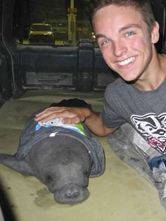 On the right you can see Mitchell Thomas, 19, and on the left you can see Mitchell, the baby manatee.
