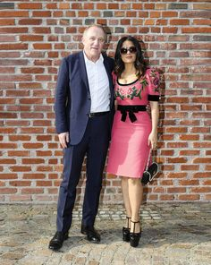 Guests from the Gucci Fall Winter 2017 fashion show in Milan, Francois Henri-Pinault and Salma Hayek Pinault in a Gucci Fall Winter 2017 embroidered dress with velvet bow and pearls and a bag with pearl and feline head detail.
