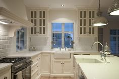 Beautiful Hamptons style kitchen. Love the subway tiles, cabinets and pendant lights.