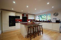 Gairich Kitchen in Ivory with African Red Granite worktops, Neff appliances and black glass splashback by Saffron Interiors. #kitchen #ivory #granite #red #black #shaker  Saffron Interiors 01483 511068 / sales@saffroninteriors.co.uk