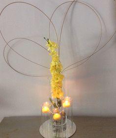 Centro de mesa amarillo con velas,cristal,y bambu