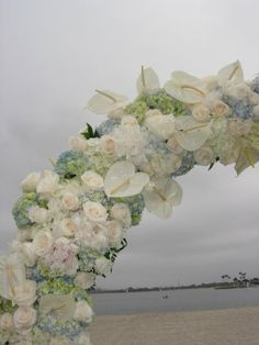A pretty arch composed of Hydrangeas, roses and white Anthuriums.