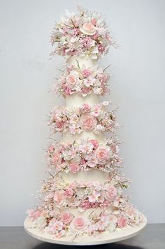 This five tiered wedding cake by Sylvia Weinstock is separated by 5 layers of delicate pink sugar flowers.