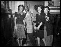 Teenie Harris  Group portrait of two women and two men, woman on right wearing dark dress with wide brimmed hat, in interior with wainscoting and pictures on wall  c. 1940-1945