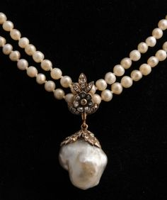 An Antique baroque natural pearl and diamond pendant on a natural pearl necklace