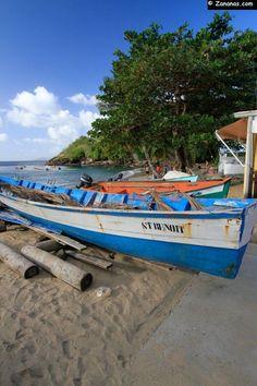 Un gommier, barque de pêche traditionnelle martiniquaise, posé sur des rondins. Anse Dufour sur la commune des Anses d'Arlet sur la côte sud caraïbe de la Martinique.