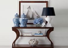 Beautiful contrast of a contemporary console with classic blue vases. They stand out against the sailboats. This is a good example of layering.