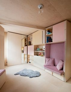 13 Square Metre House. single-storey house in north London with adjustable plywood furniture including a fold-out bed, a standing desk and extendable dining benches with pink cushions.