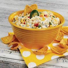 """Robert's Corn Dip   MyRecipes.com  (Also Dannon's """"Mexican Cheese Dip""""):  3 11-oz. cans sweet corn & diced peppers, drained, 2 4.5-oz. cans chopped green chiles, 1 6-oz. can chopped jalapenos, drained and liquid added to taste, 1/2 cup green onion, chopped, 1 cup mayonnaise,     1 cup sour cream,     1 teaspoon pepper ,1/2 teaspoon garlic powder, 1 16-oz. pkg. shredded sharp Cheddar cheese, corn chips Garnish: sliced jalapeno"""