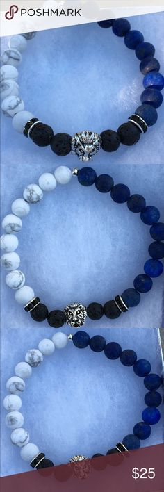 """Lapis Lazuli and White Howlite Lion Bracelet This beautiful bracelet is made with natural lapis lazuli, black lava rocks, and matte white howlite. It features a silver tone lion head in the center. This piece is on elastic and will stretch to fit up to an 8"""" wrist.   To use as an oil diffuser, add one or two drops of essential oil to each of the lava rocks. The effect will last for a couple days.   All PeaceFrog jewelry items are handmade by me! Take a look through my boutique for more…"""