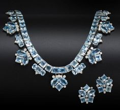 An aquamarine and diamond necklace and earring suite, by Cartier, circa 1950  The articulated row of square-cut aquamarines suspending alternating trios and chevrons of vari-cut aquamarines and brilliant-cut diamonds, to a foxtail-link backchain, together with a pair of earclips en suite, diamonds approximately 2.10 carats total, signed Cartier, necklace numbered, necklace length 41.1cm, earring length 2.4cm