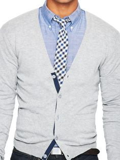 Well put together combination - a light gray cardigan over a light blue buttoned down shirt and a checkered tie, all of it with the correct accents and tones.