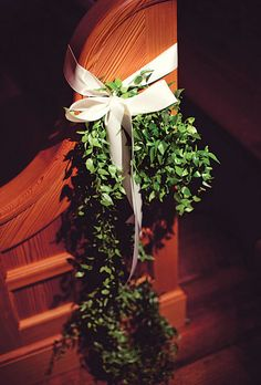 Lush Green Wedding Ceremony Decor. Lush greenery adorned with a white bow. Floral design provided by Sea Island Event Design.