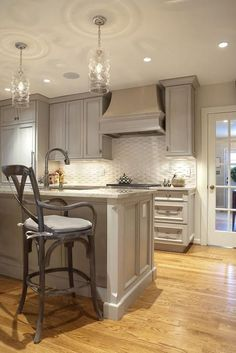Gray kitchen with gray washed cabinets paired with gray granite countertops and white basketweave tile backsplash. Kitchen features Juliska Column … …