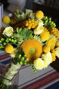 Craspedia, succulents, teddy bear sunflowers, hypericum, roses make this a fresh spring-time bouquet. • La Fleur