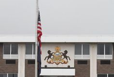 The U.S. flag is flow at half-staff outside of the Pennsylvania State Police headquarters in Dunmore, Pa., on Saturday, Sept 13, 2014. A late-night ambush outside a state police barracks in Pennsylvania's rural northeastern corner left one trooper dead and another critically wounded, and authorities scoured the densely wooded countryside and beyond on Saturday looking for the shooter or shooters. (AP Photo/ The Times-Tribune, Jake Danna Stevens)
