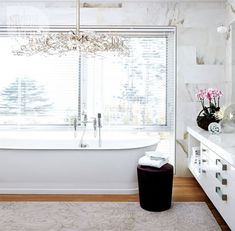Calacatta marble tiles cover the walls in the master bathroom, giving the room a decidedly warm and luxurious retreat look. The statement chandelier is a sculptural element that anchors the tub and offsets the space's clean lines.