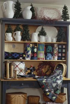 Stacking quilts one on top of another is an idea that's been around for quite some time. But rolling them up and standing them on end like books on a bookshelf? Now that's a great idea. Here, designer Alex Anderson combined white pitchers and platters and unadorned, artificial trees to add interest to the display without taking attention away from the quilts.