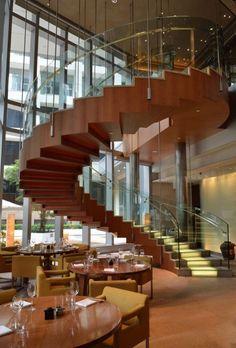 un escalier en colimaçon moderne en bois avec un garde-corps transparent