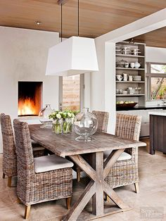 Strike a balance between cozy and sleek with a contemporary design with farmhouse references. This serenely hued dining room does that and more. A trestle table crafted from reclaimed wood and new wicker chairs make a collected statement below a thoroughly modern light fixture. A recessed firebox, dark wood ceilings, and stony floor tiles enhance warmth without disrupting the calm.