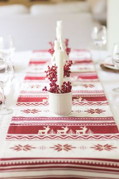 A Scandinavian-inspired Christmas tablescape with a simple red & white color scheme. White mugs, taper candles and red berries arranged along a runner.
