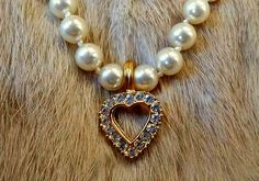 VINTAGE ROMAN 19 INCH HAND KNOTTED FAUX PEARL NECKLACE WITH HEART ENHANCER PENDANT.  EACH GLASS PEARL IS HAND KNOTTED AND A NICE HEAVY QUALITY.  THE ENHANCER HAS VIBRANT CLEAR RHINESTONES IN A NICE HEAVY GOLD TONE HEART.  ALL STONES ARE INTACT. ON THE BACK OF THE GOLDTONE BALE IT IS SIGNED ROMAN.  THE GOLDTONE DECORATIVE CLASP IS IN EXCELLENT WORKING ORDER.     THE ENHANCER MEASURES 3/4 INCHES. EXCELLENT CONDITION...ESTATE FIND LOOKS LIKE IT WAS NEVER WORN, GREAT GIFT OR TO ADD TO YOUR OWN…