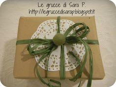 Pacco regalo con nastro di rafia verde, pizzo di carta e biglia di feltro