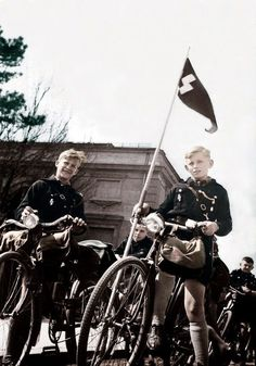 "Boys of the Hitler Youth ride their bicycles through the German Reich's capital of Berlin and are led by the unit leader in front with the Hitler Youth single ""Schutze"" rune mounted to his bicycle. This is part of a training exercise meant to teach the Youth the importance of maintaining organization within a mobile unit. Summer, 1938."