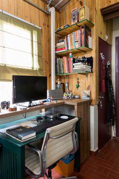 Casa pequena, casa charmosa, detalhes da decoração do home office com revestimento de madeira, mesa verde, cadeira branca.