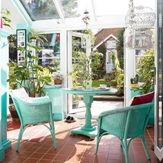 Conservatory with green painted wicker furniture