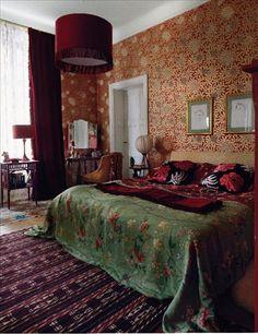 Budoirstämning i det stora sovrummet med tapet  från Osborne&Little. På sängen ligger ett grönt linnetyg från Baker. Röd, mönstrad textil från basaren i Istanbul och kuddar från Urban outfitters. Golvet täcks av kelimmattor köpta för 25 år sedan på Ikea. I taket hänger en enkel lampskärm som fått fransar. Porträtten av Charlotte och Janne tecknade Adam som fyraåring. Sminkbord från Myrorna med förhänge från Manuel Canovas. Emmafåtöljen och det röda bordet är också Myrornafynd, röd lampa…