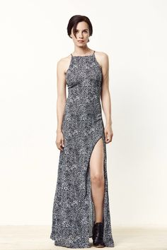A sophisticated and stunning printed maxi dress featuring a high neck, adjustable straps, and a high front, sexy slit. This dress has a full lining and a side z
