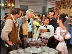 Hoss and Adam escorting Little Joe off the premises before he drowns himself in the punch bowl...or gets shot by Doc Holiday. From Calamity Over the Comstock (Bonanza)