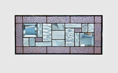 This stained glass panel window is a geometric abstract with several different textures of clear glass with a pale purple mauve border. There are 2 - 3 x 3 bevel squares in the corners. The panel is 8 1/4 x 18 1/4 inches. The patina on the solder is done in black and the frame is zinc left in a silver tone. There are rings on top so that the piece can be hung in either direction. To see more abstract geometric panels http://www.etsy.com/shop/sghovel?section_id&#...