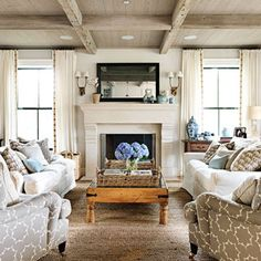 """A pair of oversize sofas, slipcovered in canvas and piled high with pillows, helps make the family room a cozy haven. Jane arranges her collection of blue-and-white Chinese ginger jars on the mantel and side table along with favorite photos. She picked Benjamin Moore Pale Oak for the walls and painted the reclaimed-wood coffered ceiling a complementary driftwood shade. """"Neutrals are the most calming and help pull a room together."""" The mirror above the fireplace hides a flatscreen TV…"""