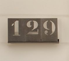 """Stencil House Numbers $14.00  These numbers are modern looking and traditional at the same time. They stand out with the heavy metal surrounding the stenciled numbers. They would stand out on a front porch column.Dimensions & Details Details 2-Number Track: 8.5"""" wide x 2.5"""" deep x 1"""" high 3-Number Track: 12.5"""" wide x 2.5"""" deep x 1"""" high Includes two screws and two wall anchors for mounting. Number plates slide onto the track.
