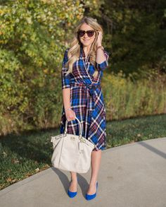 A blue and red plaid dress from Karina Dresses is paired with blue suede heels and an off white bag for a fall business casual look.
