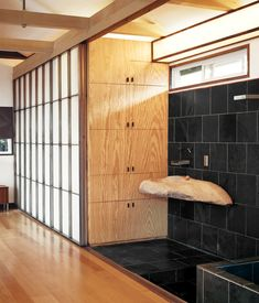 Custom shoji-inspired screens of Roberts's design conceal the closet and extend to provide privacy for the adjacent shower and soaking tu...