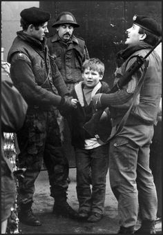 A young boy is held by British soldiers from the Gloucester Regiment after he was caught in the act of hurling stones at a Saracen Armoured Personal Carrier in the IRA (Irish Republican Army) stronghold, the lower Falls Road area, March 1972, Belfast, Northern Ireland. The boy claimed he was paid by extremists to toss rocks at the British troops.