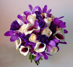 """""""Bi-colored Picasso Calla Lilies combined with ivory roses, rich purple Lisianthus and exotic purple Mokara orchids in the wedding bouquet"""""""