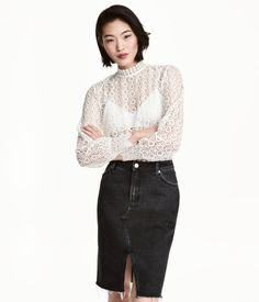 White. Lace blouse with a stand-up collar with buttons at back and long sleeves with wide cuffs.