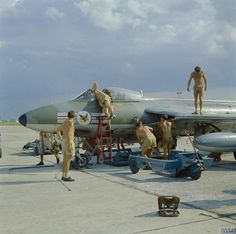 Ground crew work on a Hawker Hunter FGA.9 aircraft of 20 Squadron RAF at RAF Tengah, Singapore.