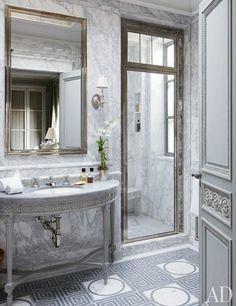 In the master bath, hand-carved details distinguish a custom-made vanity; the sink fittings and door hardware are by P. E. Guerin, and the marble-mosaic floor tile is by Smith for Ann Sacks.