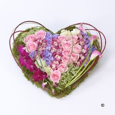 A beautiful funeral flower arrangement. This heart-shaped design including large-headed roses, carnations and cymbidium and dendrobium orchids is given a contemporary feel with sweeping pink calla Lily, cornus and steel grass | Booker Flower and Gifts, Liverpool | Free Flower Delivery Liverpool