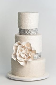 Silver pearls and an oversized flower punctuate this three-tiered Sugar Couture cake covered in soft pink edible glitter.