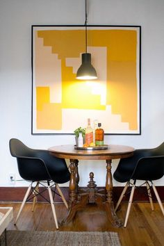 dining for two... found table with mod chairs, love! and love the bright yellow geometric painting, keeps it mod, love round table tray to keep kitchen table elements together